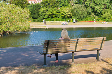 Back view of blonde woman seated on a bench along the lake