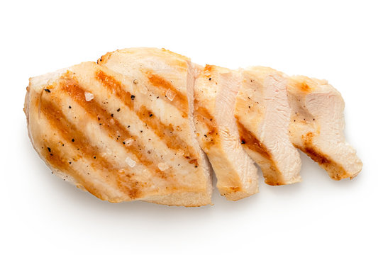 Partially sliced grilled chicken breast with grill marks, ground black pepper and salt isolated on white. Top view.