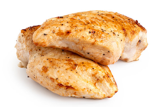 Two whole pan roasted chicken breasts isolated on white.