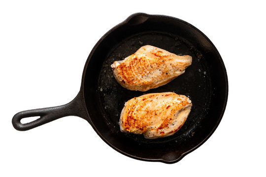 Two whole chicken breasts roasting in cast iron pan isolated on white. Top view.