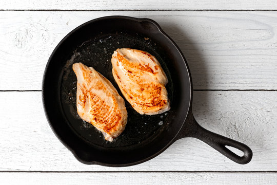 Two whole chicken breasts roasting in cast iron pan isolated on white wood. Top view.