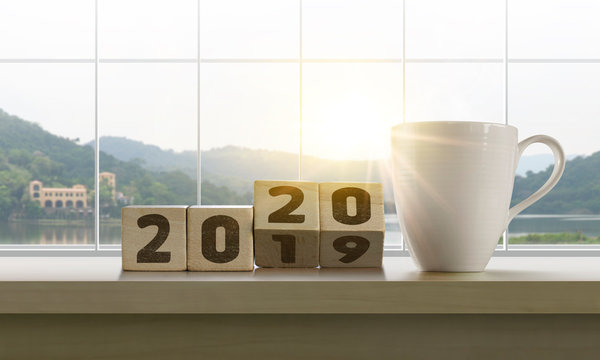Wooden blocks with the word 2020 and coffee on table with panoramic lake landscape background in the morning. Happy New Year, start up, refresh, mindset concept.
