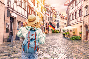 Young asian woman tourist traveling with german flag near the famous half-timbered street in Nuremberg old town Fototapete