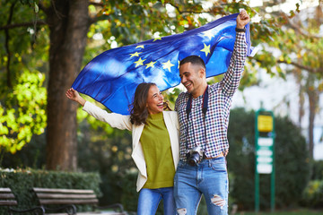 Happy young couple of tourists with a European Union flag