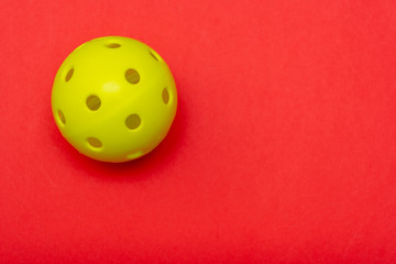 Bright yellow pickleball or whiffle ball on a solid bright red flat lay background symbolizing sports and activity with copy space.