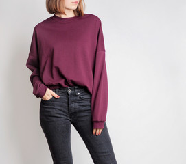 Young woman wearing simple outfit with oversized burgundy sweatshirt and black high-waisted jeans isolated on light grey background. Copy space
