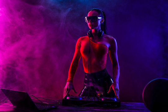 Young sexy woman dj playing music. Headphones and dj mixer on table. Colorful Smoke on background