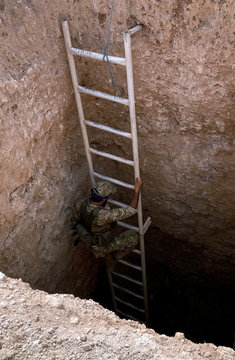 A Turkey-backed Syrian rebel fighter uses a stair to go down to an underground tunnel said to be made by the Syrian Democratic Forces (SDF) in Tal Abyad