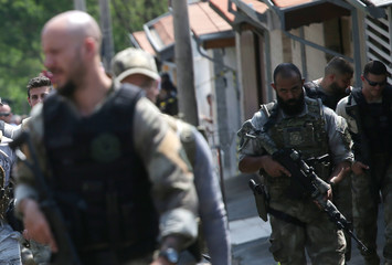 Federal police officers are seen near a site where an armed gang holds people hostage after they robbed a securities company at the Viracopos airpoart freight terminal, in Campinas