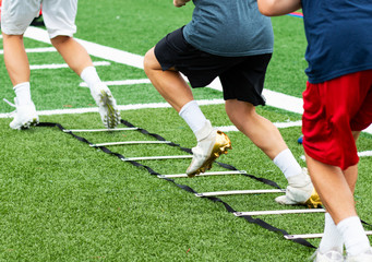 Three athletes in cleats doing ladder foot drills on turf field