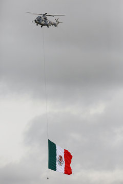 A military helicopter hovers with a Mexican flag during an official event to mark the beginning of the construction of a new international airport, at the Santa Lucia military airbase in Zumpango