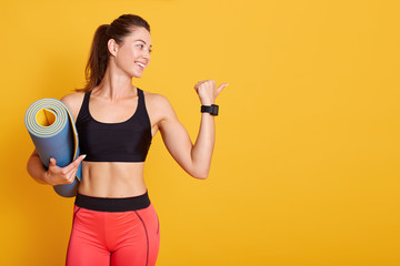 Profile portrait of young woman holding mat and shows muscles, sporty female looking aside, wearing stylish sportwear, poses smiling in studio isolatedover yellow background. Healthy lifestyle concept