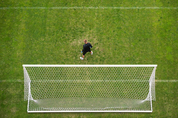 Soccer goalkeeper in front of goal - view from above