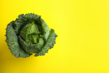 Fresh savoy cabbage on yellow background, top view. Space for text
