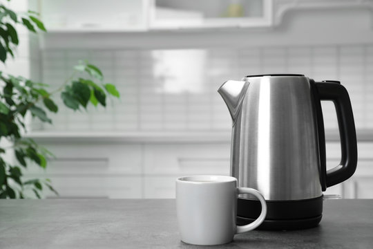 Modern electric kettle and cup on grey table in kitchen. Space for text