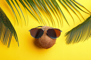 Coconut with sunglasses and palm leaves on yellow background, flat lay