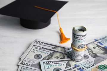 Dollar banknotes and student graduation hat on white wooden background. Tuition fees concept