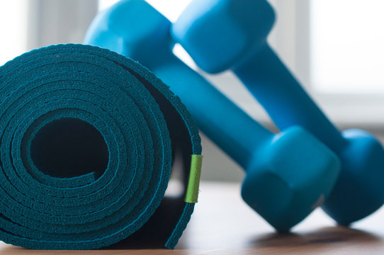 A blue rolled yoga mat. Two blue 2 kg dumbells resting on it. Fitness equipment for home exercise and flexibility training.