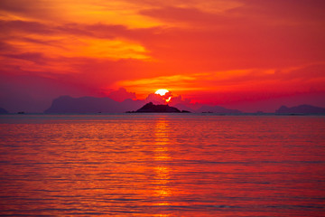 Photo sur Aluminium Rouge Beautiful colorful sunrise at the sea with dramatic clouds and sun shining