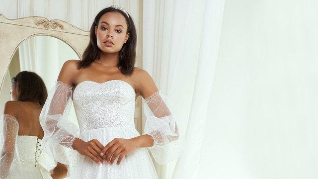 Dark-skinned bride posing in a wedding dress