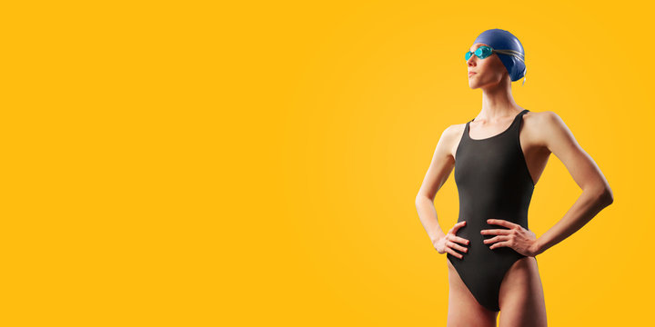 Young female swimmer portrait of half body in black swimsuit with goggle and swimming hat. Akimbo posing in studio. Isolated on yellow background