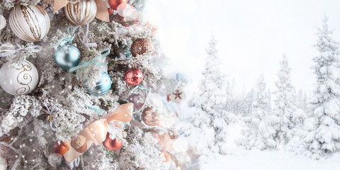 Christmas white tree decoration with Christmas toys, panoramic photo, the second part of the photo is a snowy forest in defocus, space for text. New Year card