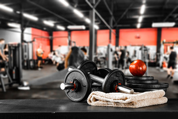 Dumbbell, barbell and workout in the gym. Space for products and decorations or text with blurred gym background.