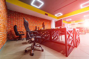 Modern office room, Design of a working place. Brick wall background. Wooden style table.