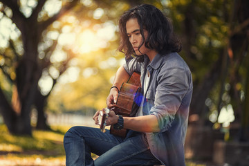 Asian long haired man is playing the guitar while he is traveling. With a rustic background and trees Under the soft sunlight in the day