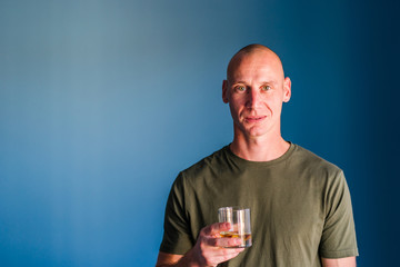 Portrait of young handsome man with short hair holding a glass of whiskey or brandy alcohol drink standing in front of blue wall looking to the camera