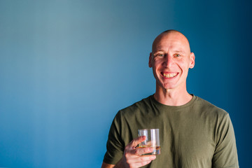 Portrait of young handsome man with short hair holding a glass of whiskey or brandy alcohol drink standing in front of blue wall looking to the camera smiling