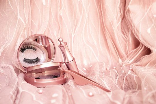 Magnetic fake artificial eyelashes in pink mirror kit, eye liner, tweezers isolated on pink background. Eyelash extension cosmetology tool concept, beauty treatment, improving physical appearance
