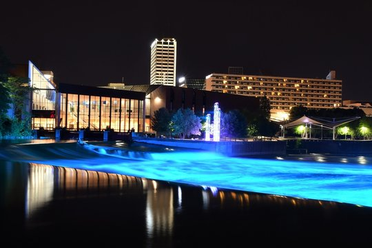 Panoramic view of downtown South Bend Indiana at night with the St Joseph river in the foreground, Century Center in the background and the St Joseph river lights on.