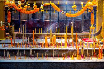 Incense and burning candles at the Erawan Shrine in Bangkok, Thailand