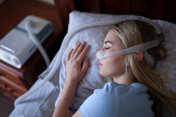 Young person, sleeping with cpap machine.