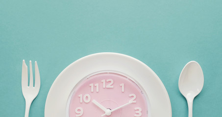 Pink clock on white plate, Intermittent fasting concept, ketogenic diet, weight loss, skip meal