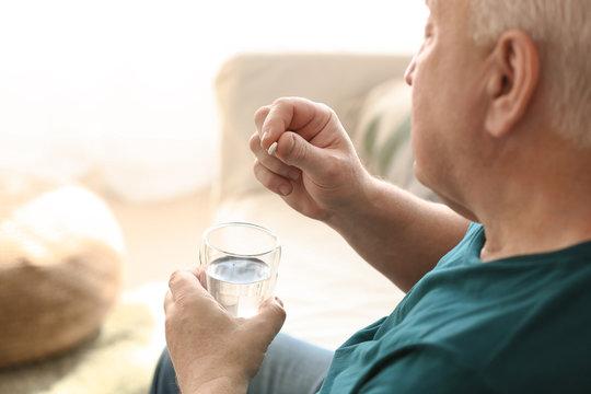 Elderly man taking medicine at home