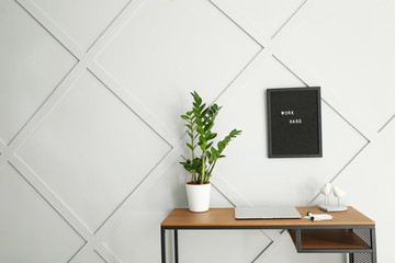 Modern stylish workplace near grey wall