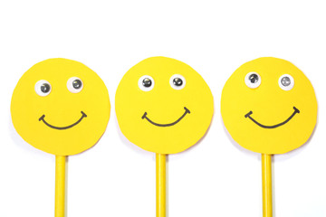 Group of happy yellow smiley faces on white background