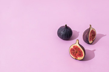 halves of figs on a pink background. the background. healthy eating concept