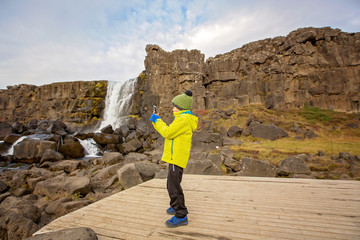 Cute child, boy, enjoying a sunny day in Thingvellir National Park rift valley,taking pictures with cellphone, Iceland