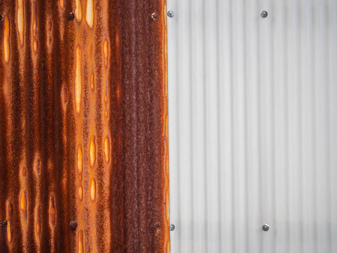 Abstract and closeup the different of old rusty and new aluminum zinc sheet wall background and texture with vertical striped or wave pattern. Contrast or difference concept.