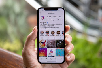 Man hand holding iPhone X with social networking service Instagram