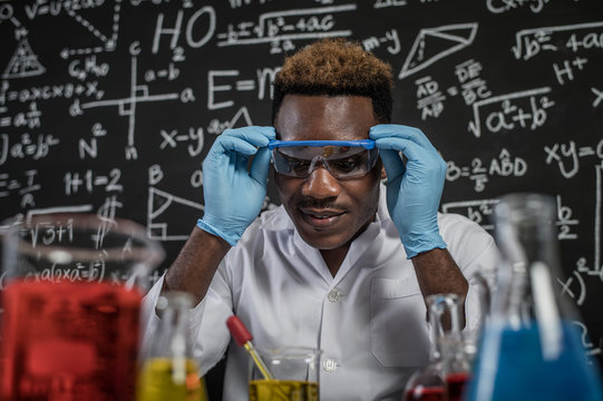 Scientists look at the yellow chemical in the glass at the laboratory and hand handle the glasses.