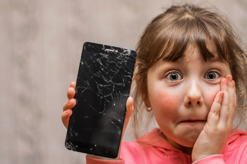 Obraz Portrait of a scared little girl with a broken mobile phone. A sad child broke the screen of a mobile phone. Cracked display in hand kids. The frightened child accidentally ruined the smartphone - fototapety do salonu