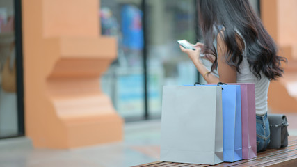 Shopping bag placed on a wooden seat with  shoppers are searching for information with smartphones on background.