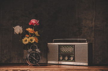 retro radio receiver are still life with clocks and flower vases.