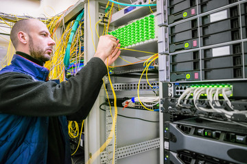 An engineer connects magistral optical fiber wires. A man commutes Internet wires in a server rack. The system administrator works in the server room of the data center.