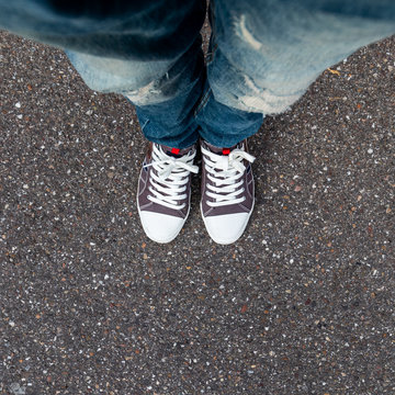 A young man's legs dressed in jeans and tennis on a background of asphalt.
