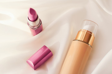 Beige tonal cream bottle make-up fluid foundation base and pink lipstick on silk background,...